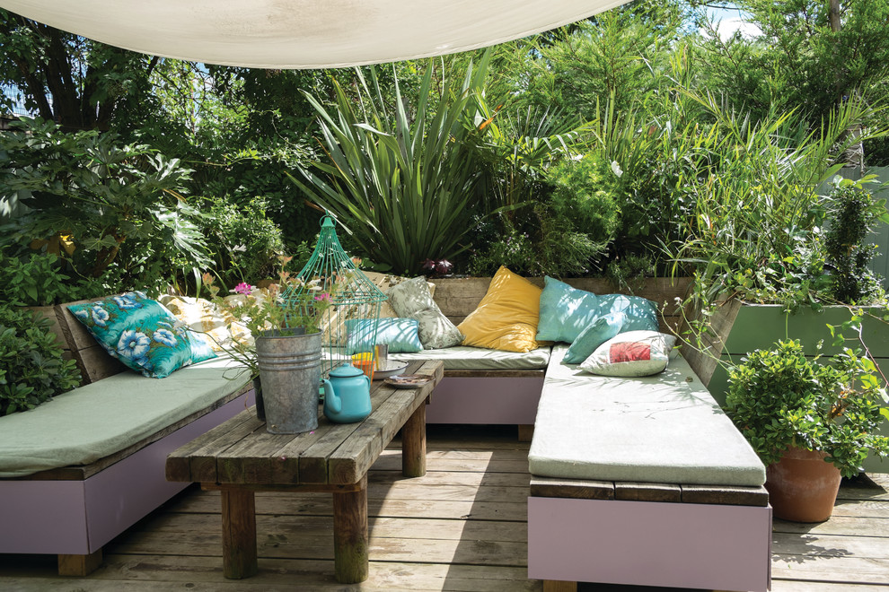 Eclectic backyard deck container garden photo in Dorset with an awning