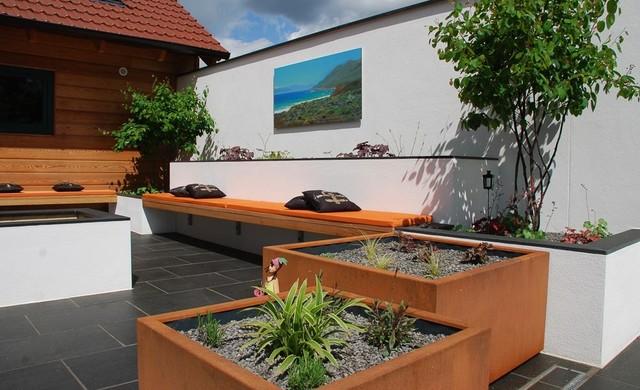Garten Lounge mit bepflanzten Kübeln, Sitzbank und Feuerstelle ...