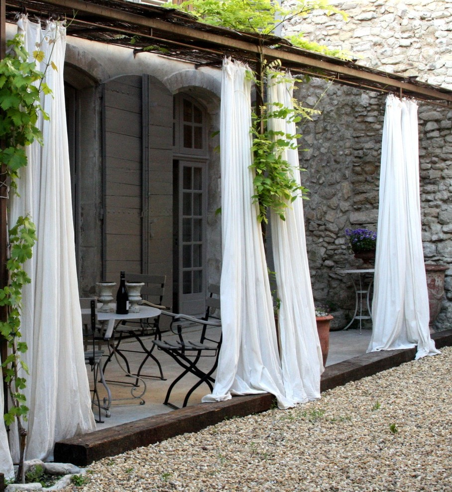 Patio - mid-sized shabby-chic style patio idea in Other with a pergola