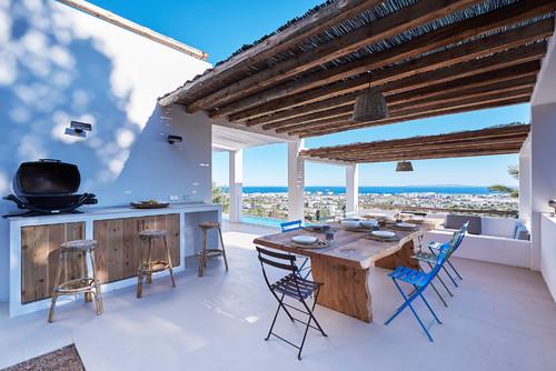 comedor en una terraza con chimenea y toques azules