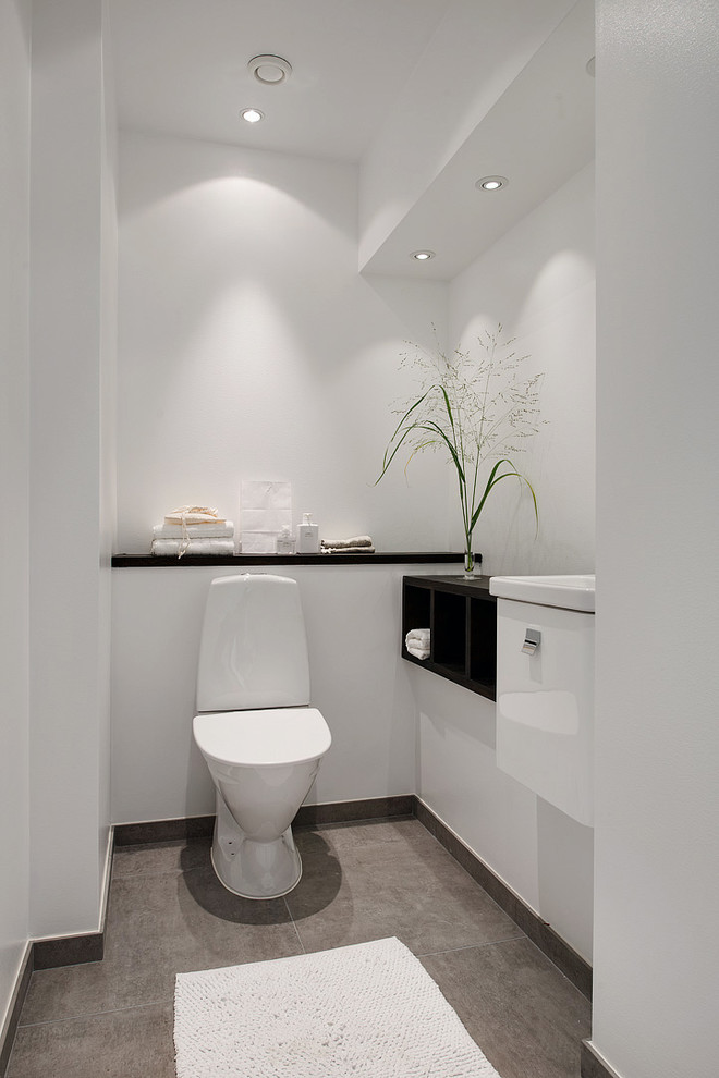 Inspiration for a mid-sized scandinavian gray floor powder room remodel in Gothenburg with flat-panel cabinets, white cabinets and a two-piece toilet