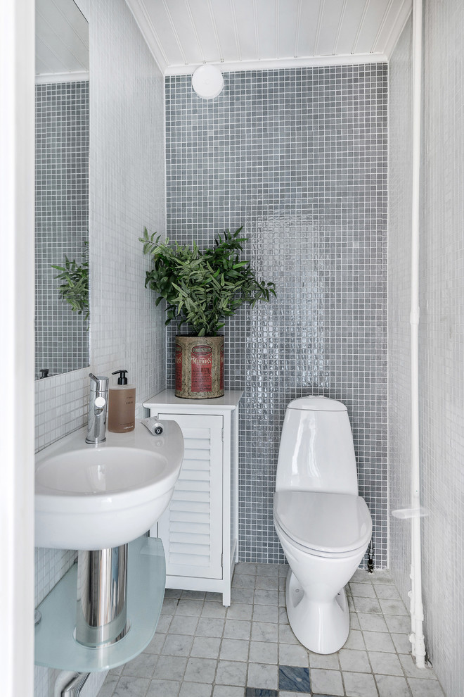 Example of a small danish gray tile and mosaic tile multicolored floor powder room design in Stockholm with a one-piece toilet, gray walls and a wall-mount sink