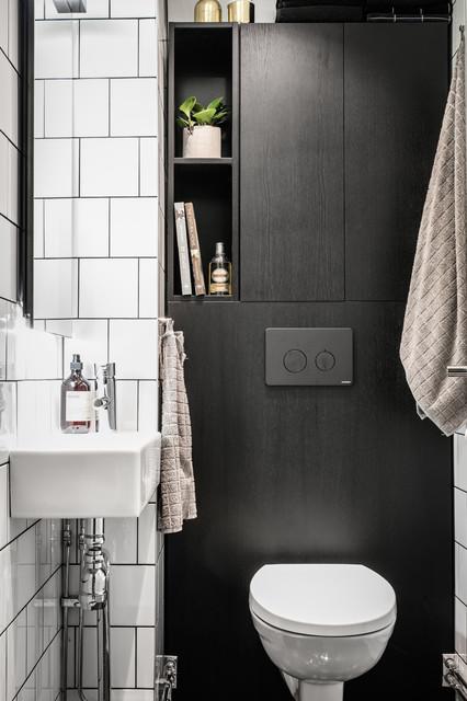 Foto på ett litet nordiskt badrum, med en toalettstol med separat cisternkåpa, vit kakel, keramikplattor, vita väggar och ett väggmonterat handfat