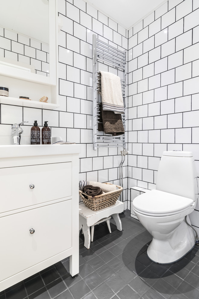 Inspiration for a mid-sized scandinavian white tile and porcelain tile gray floor powder room remodel in Other with flat-panel cabinets, white cabinets, a two-piece toilet, white walls and an integrated sink