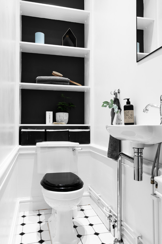Inspiration for a small transitional multicolored floor powder room remodel in Stockholm with open cabinets, a one-piece toilet, a wall-mount sink and black walls