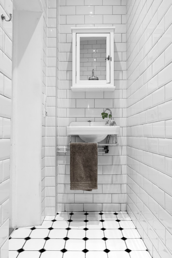 Inspiration for a small scandinavian white tile and subway tile multicolored floor powder room remodel in Stockholm with white cabinets, white walls and a wall-mount sink