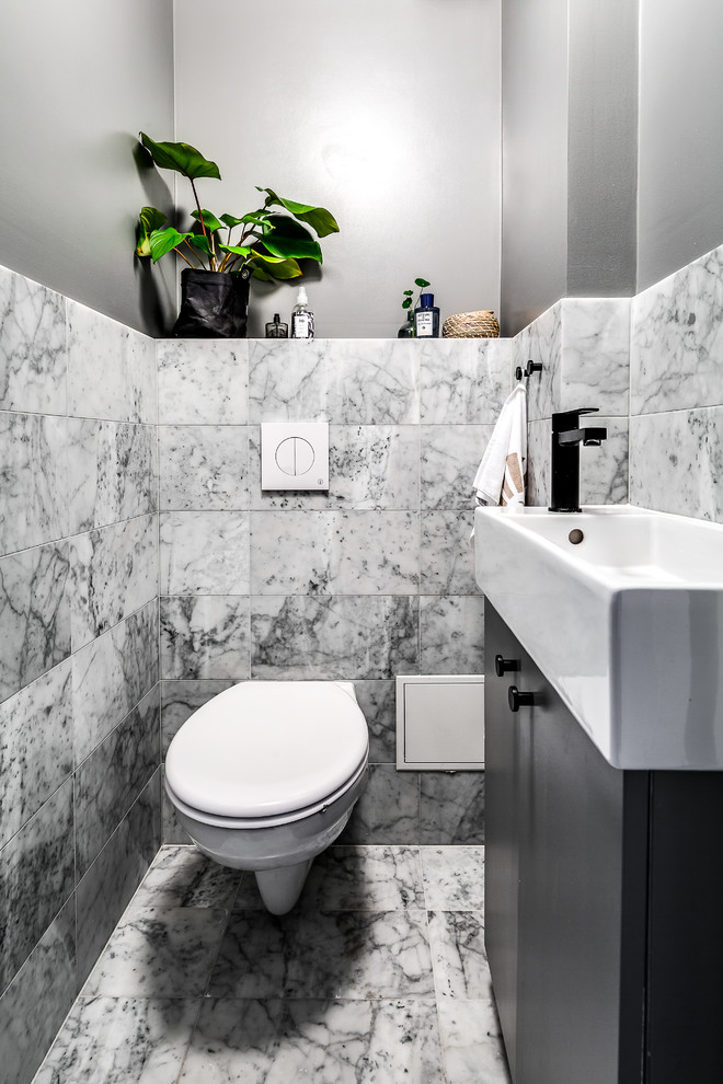 Inspiration for a scandinavian powder room remodel in Stockholm with black cabinets, a wall-mount toilet and a trough sink