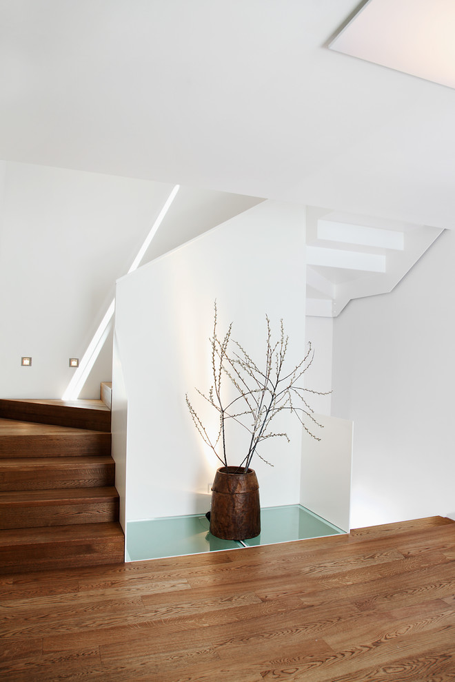 Mid-sized trendy wooden curved staircase photo in Munich with wooden risers