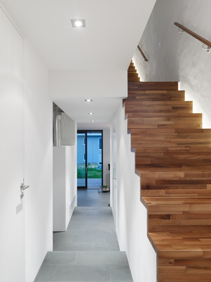 Large trendy wooden straight staircase photo in Berlin with wooden risers