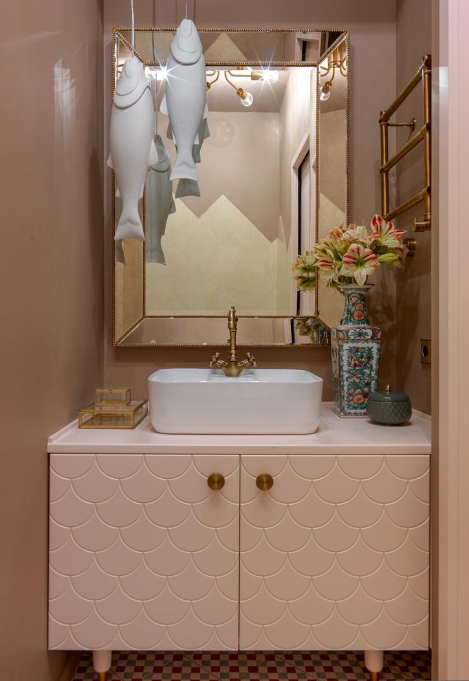 Idée de décoration pour un WC et toilettes design avec un mur beige, une vasque, un sol multicolore, un placard à porte plane et un plan de toilette rose.