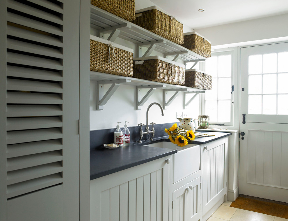 Inspiration for a farmhouse travertine floor laundry room remodel in Wiltshire with a farmhouse sink, shaker cabinets, granite countertops and a concealed washer/dryer
