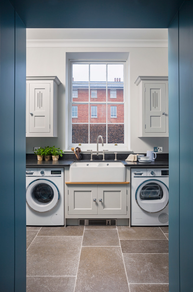 This is an example of a medium sized classic utility room in Hampshire with grey cabinets, granite worktops, black splashback, limestone flooring, shaker cabinets and a belfast sink.