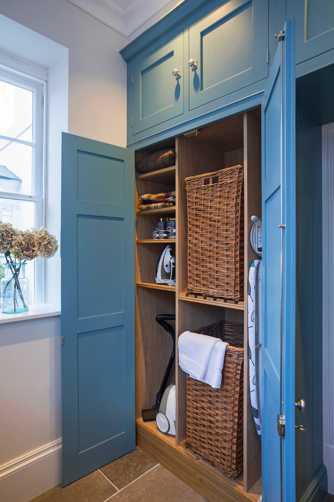 Inspiration for a mid-sized transitional limestone floor laundry room remodel in Hampshire with blue cabinets and shaker cabinets