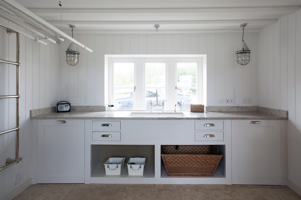 Inspiration for a mid-sized coastal laundry room remodel in Wiltshire with an undermount sink, shaker cabinets, white cabinets and white walls