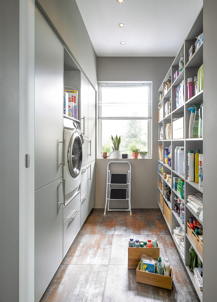 Utility room - contemporary galley gray floor utility room idea in Other with flat-panel cabinets, white cabinets and white walls
