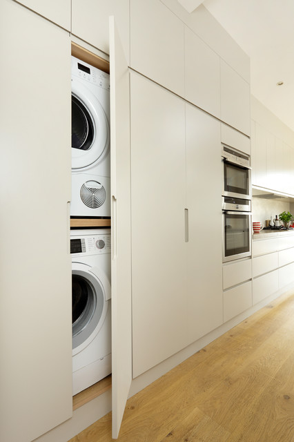 Inspiration for a contemporary laundry cupboard in London with flat-panel cabinets, beige cabinets and a stacked washer and dryer.