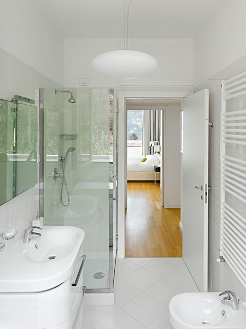 Immagine di una stanza da bagno con doccia contemporanea di medie dimensioni con ante lisce, ante bianche, piastrelle bianche, piastrelle in ceramica, pareti bianche, pavimento con piastrelle in ceramica, lavabo integrato, doccia ad angolo e WC sospeso
