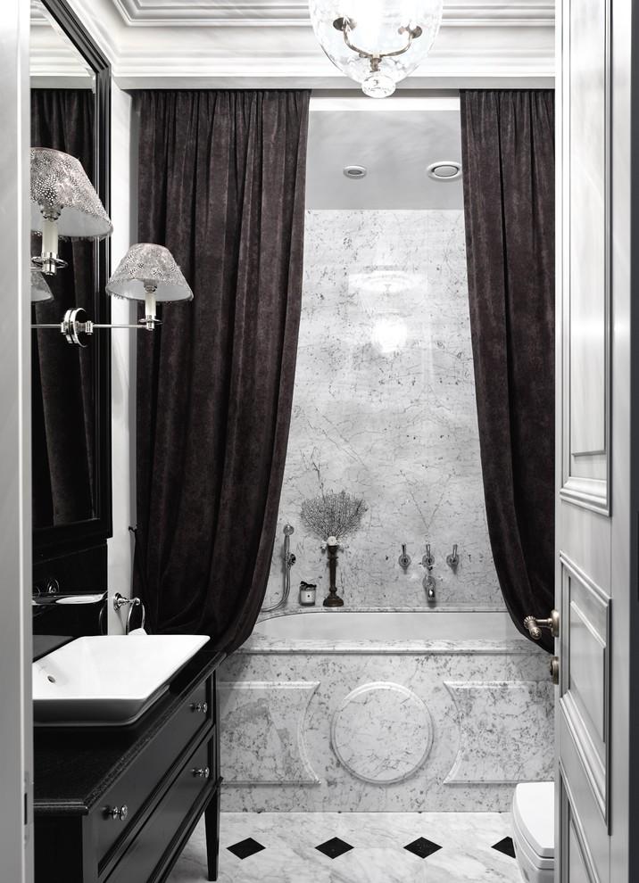 Foto de cuarto de baño principal, tradicional, de tamaño medio, con armarios con paneles empotrados, puertas de armario negras, bañera empotrada, combinación de ducha y bañera, paredes grises y lavabo sobreencimera