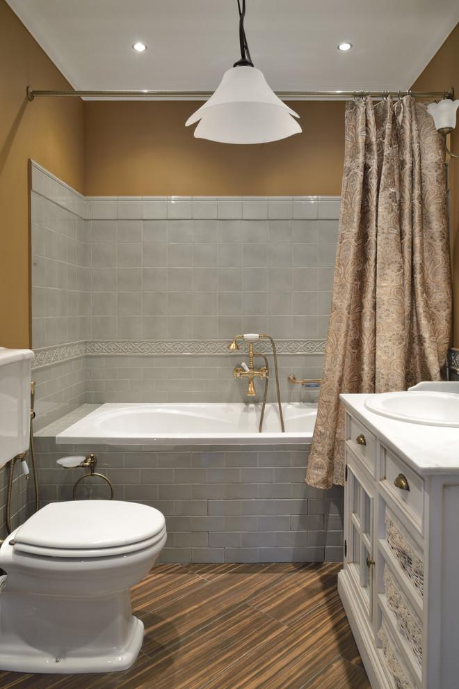 Стильный дизайн: главная ванная комната в классическом стиле с фасадами с утопленной филенкой, белыми фасадами, ванной в нише, душем над ванной, раздельным унитазом, серой плиткой, коричневыми стенами, накладной раковиной, коричневым полом, шторкой для душа и белой столешницей - последний тренд