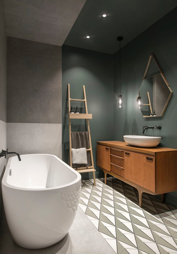Large danish master gray tile and porcelain tile cement tile floor and multicolored floor freestanding bathtub photo in Saint Petersburg with green walls, a vessel sink, wood countertops, medium tone wood cabinets, flat-panel cabinets and brown countertops