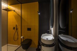 Salle de bain avec un carrelage jaune et un mur noir ...