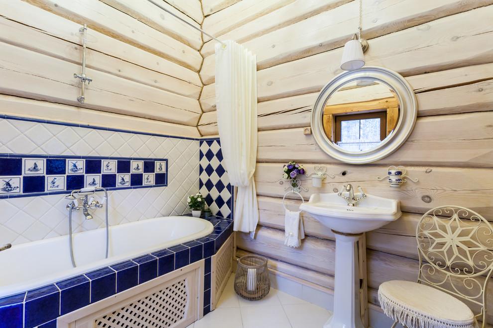 Foto de cuarto de baño rural con baldosas y/o azulejos azules, baldosas y/o azulejos blancos, lavabo con pedestal, bañera encastrada, combinación de ducha y bañera, paredes blancas y ducha con cortina