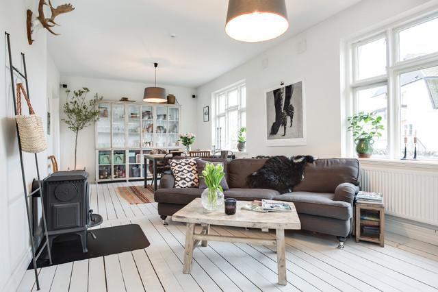 Bild på ett stort skandinaviskt allrum med öppen planlösning, med vita väggar och målat trägolv