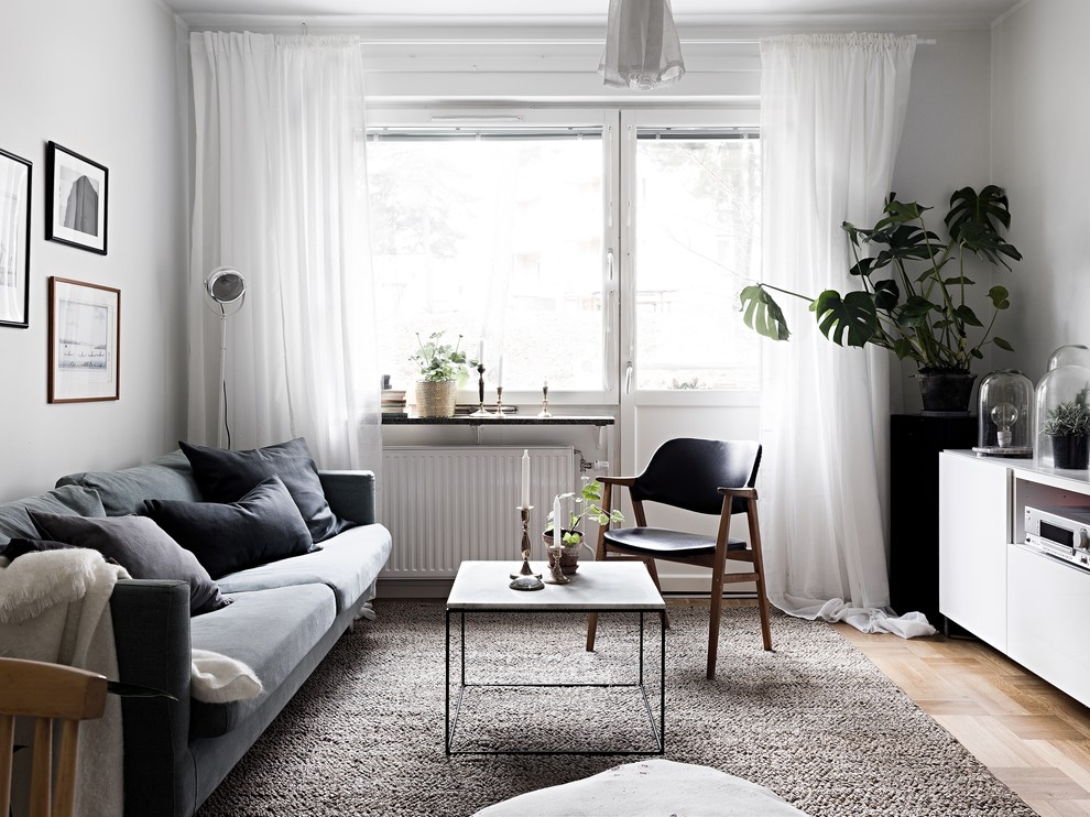 Living room - mid-sized scandinavian formal and enclosed light wood floor living room idea in Stockholm with white walls, no fireplace and no tv
