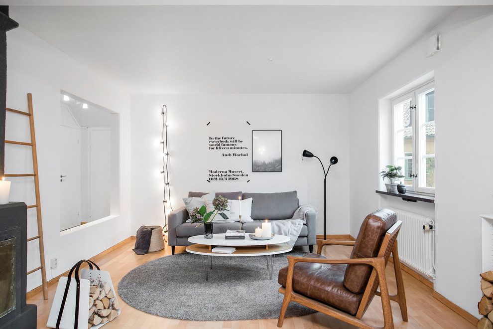 Mid-sized danish enclosed and formal light wood floor living room photo in Malmo with white walls