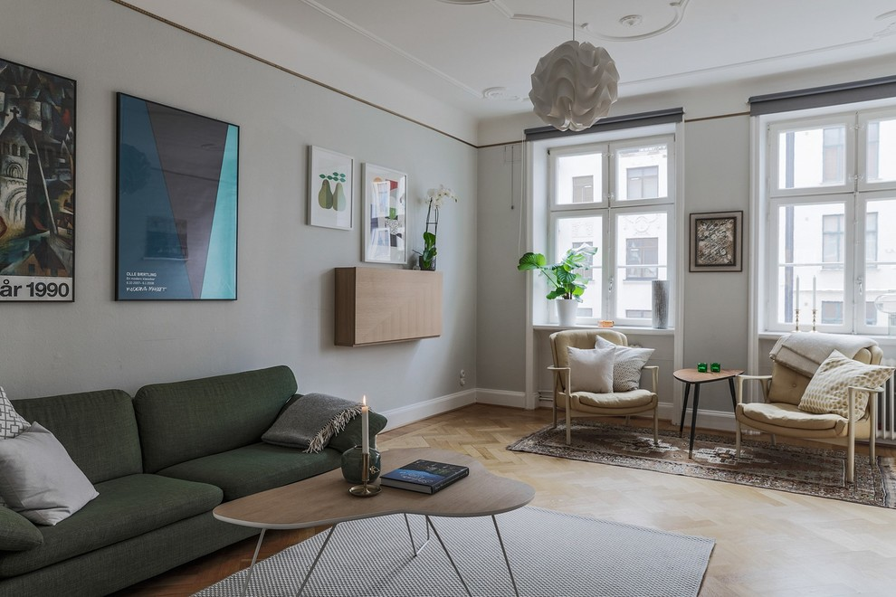 Example of a danish light wood floor and beige floor living room design in Malmo with gray walls