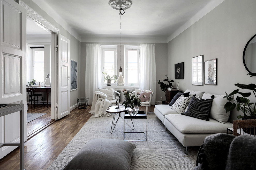 Example of a mid-sized danish enclosed medium tone wood floor and brown floor living room design in Gothenburg with white walls and no fireplace