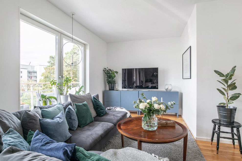 Inspiration for a small scandinavian medium tone wood floor and brown floor living room remodel in Stockholm with white walls and a tv stand