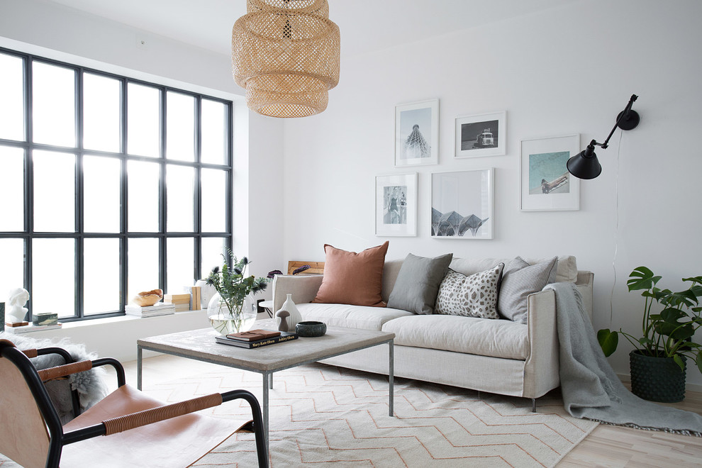 Mid-sized danish formal light wood floor living room photo in Stockholm with white walls