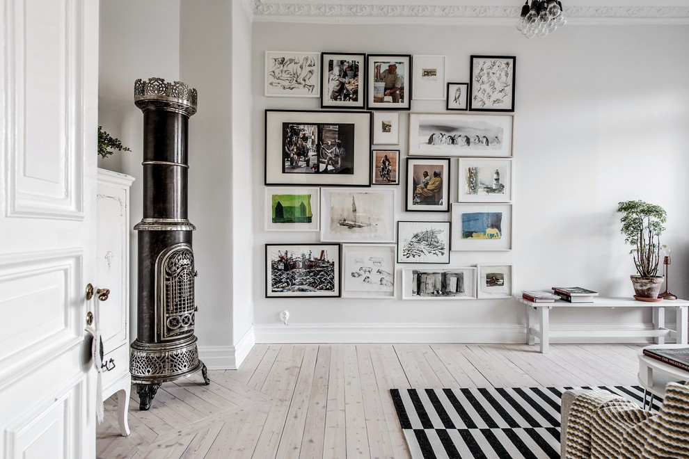 Example of a danish light wood floor and beige floor living room design in Gothenburg with white walls, a wood stove and a metal fireplace