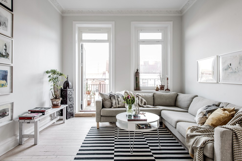 Inspiration for a mid-sized scandinavian enclosed light wood floor and beige floor living room remodel in Gothenburg with white walls