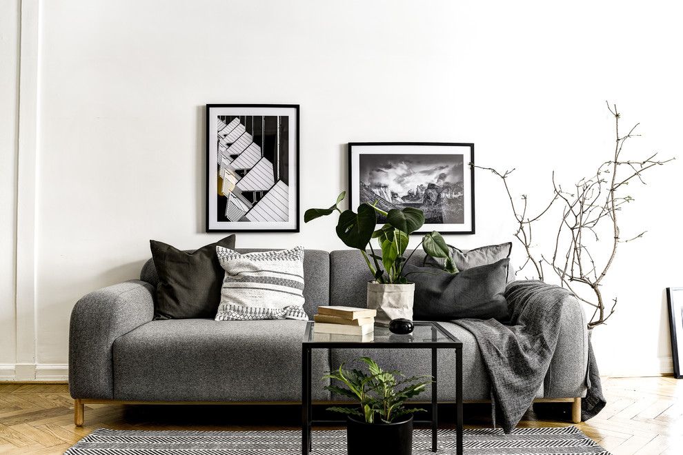 Mid-sized danish formal and enclosed medium tone wood floor living room photo in Stockholm with white walls