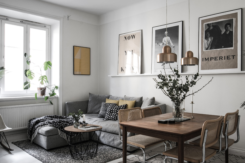 Example of a danish open concept gray floor living room design in Stockholm with gray walls