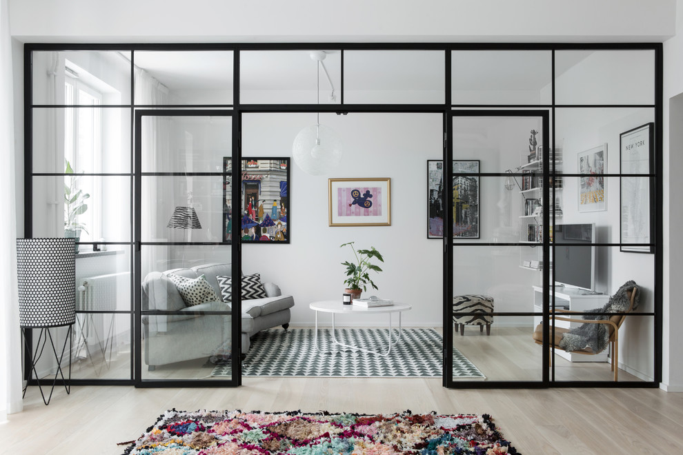 Mid-sized eclectic open concept light wood floor living room photo in Stockholm with white walls