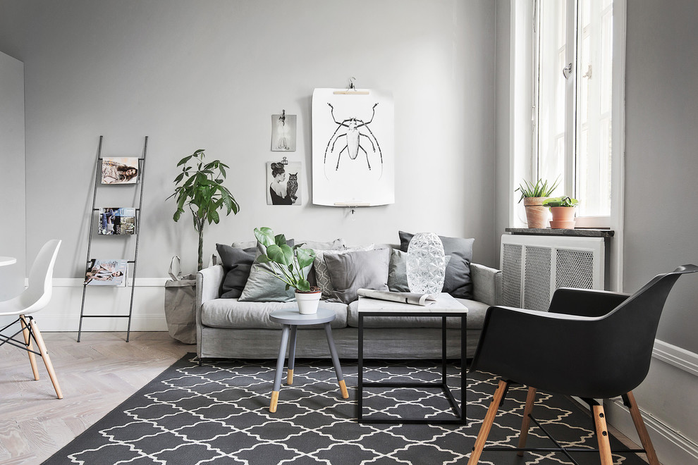 Example of a mid-sized danish formal light wood floor living room design in Stockholm with gray walls and no tv