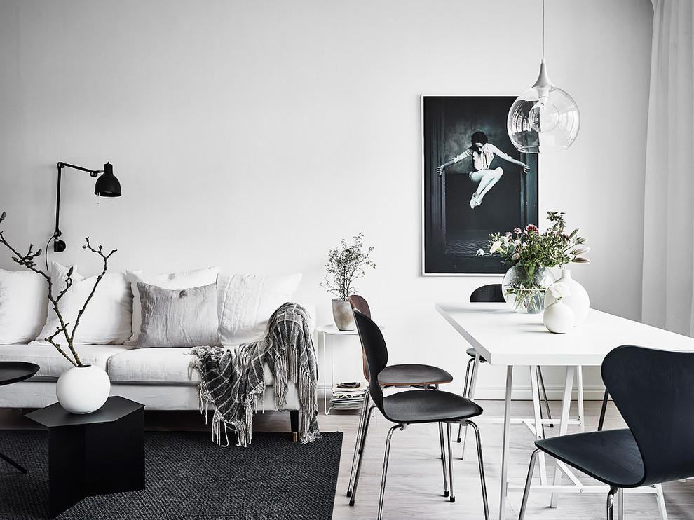 Living room - scandinavian light wood floor living room idea in Gothenburg with white walls