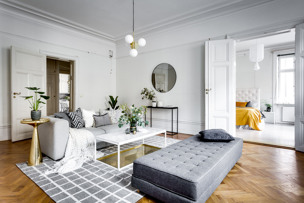 Inspiration for a scandinavian formal enclosed living room in Stockholm with white walls, medium hardwood flooring and brown floors.