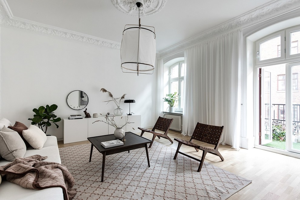 Inspiration for a scandinavian light wood floor and beige floor living room remodel in Gothenburg with white walls