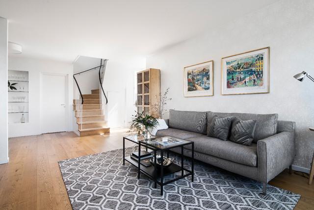 Inredning av ett skandinaviskt vardagsrum, med grå väggar, mellanmörkt trägolv och brunt golv