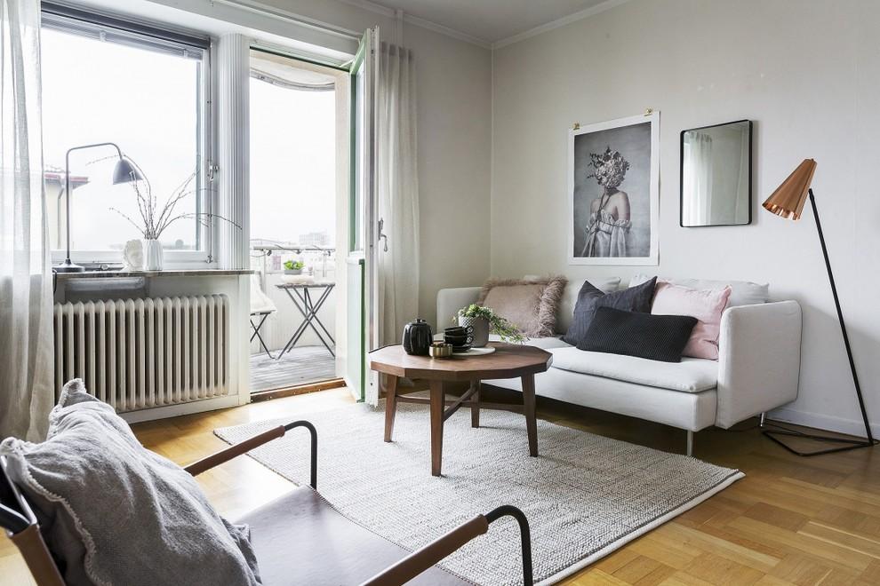 Danish light wood floor and beige floor living room photo in Stockholm with white walls