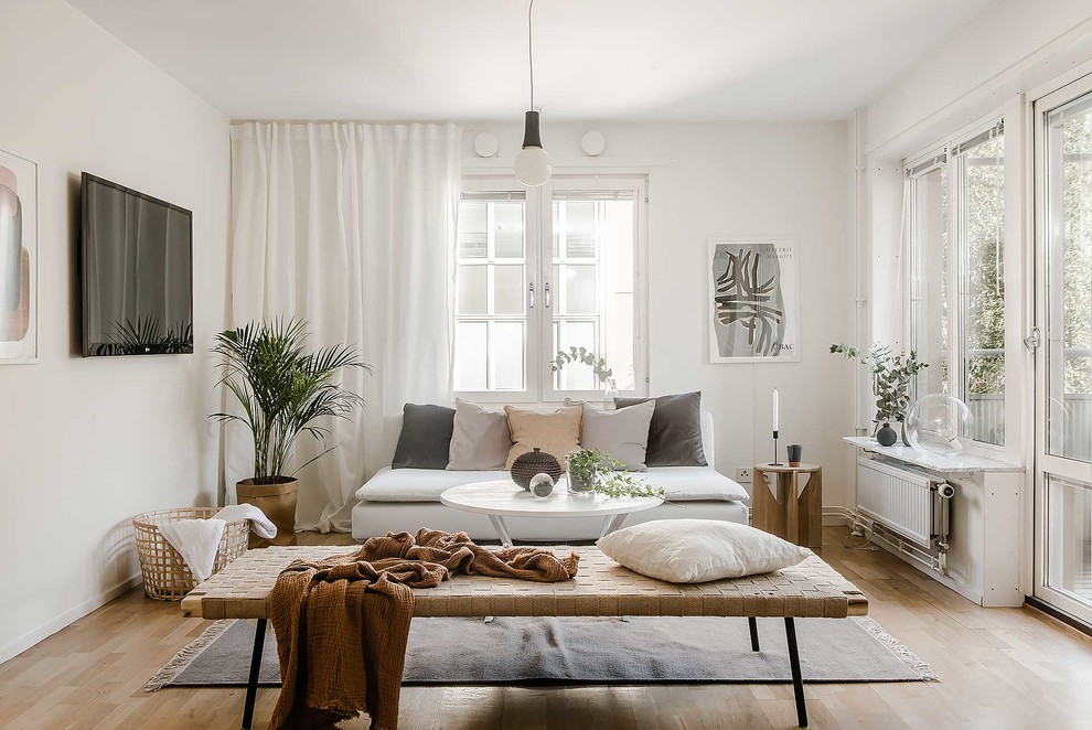 Mid-sized danish enclosed light wood floor living room photo in Stockholm with white walls, no fireplace and a wall-mounted tv