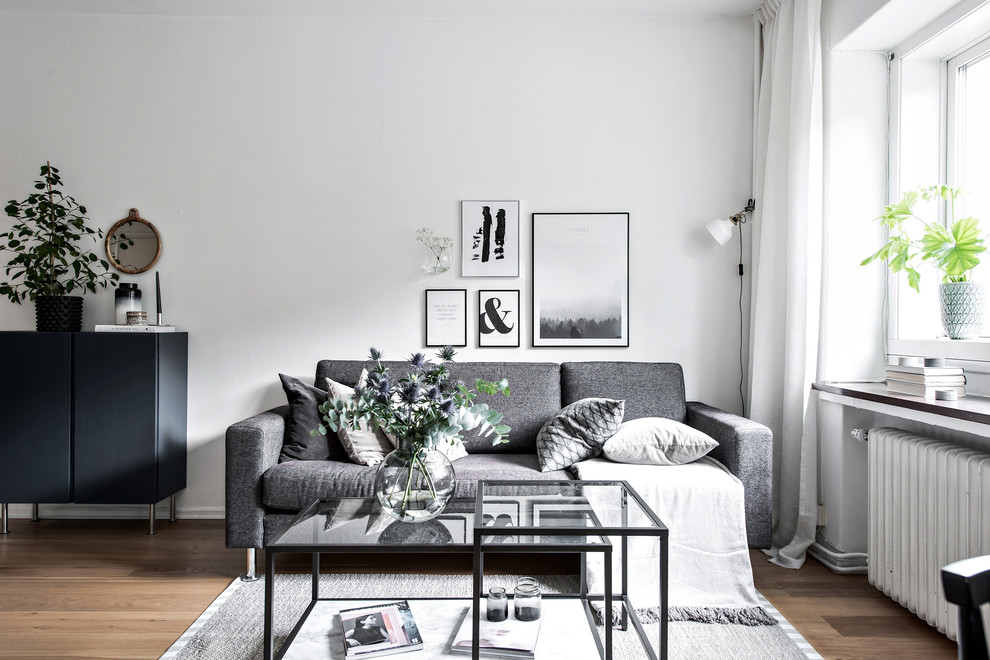 Inspiration for a small scandinavian enclosed medium tone wood floor and brown floor living room remodel in Gothenburg with white walls