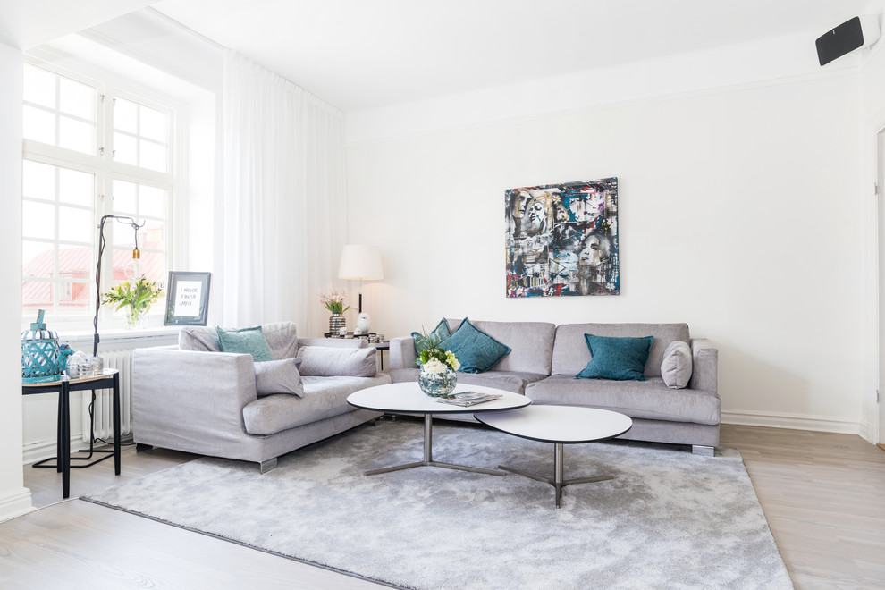 Inspiration for a mid-sized scandinavian formal and open concept light wood floor living room remodel in Stockholm with white walls and no tv