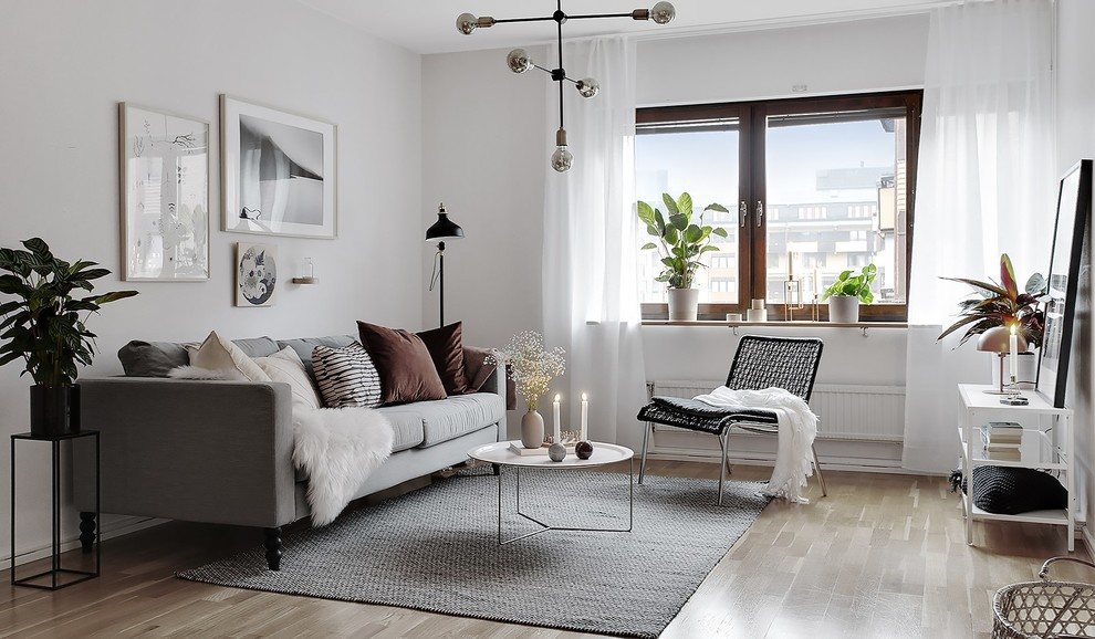 Example of a danish enclosed light wood floor and beige floor living room design in Stockholm with white walls