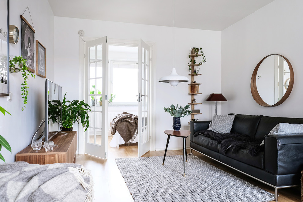 Example of a mid-sized danish enclosed medium tone wood floor and brown floor living room design in Gothenburg with white walls, no fireplace and a tv stand