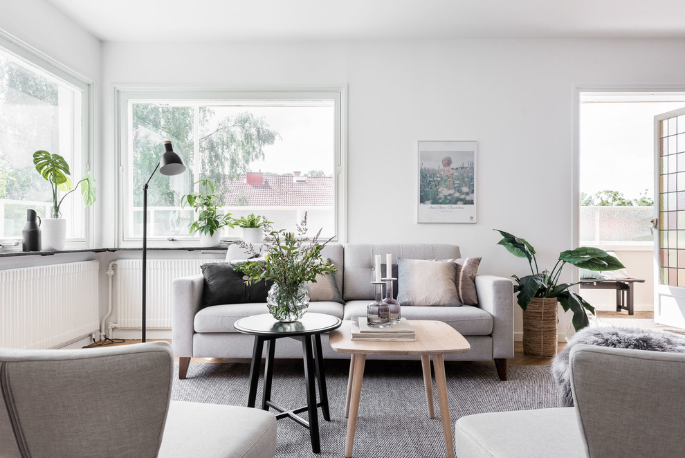 Example of a mid-sized danish formal medium tone wood floor living room design in Gothenburg with white walls and no tv